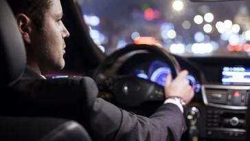 businessman driving a car at night