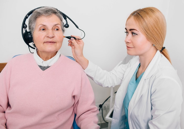 Woman Audiologist Performing Exam on Patient